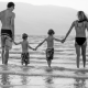 dad, two sons, and wife holding hands while wearing swimsuits in shallow water on a beach